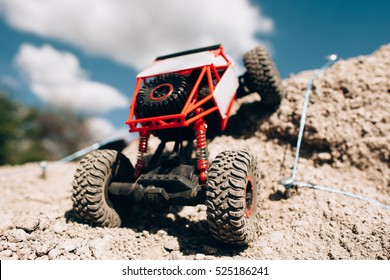 Rc car overcoming rock hill close-up. Crawler rising on rough surface of rocky rally track. Competitions radio-controlled toys concept