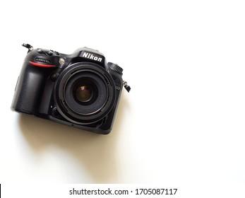 RCT, UK / April 15th 2020 : Old battered Nikon crop-sensor dslr camera with 35mm lens isolated on white desk.
