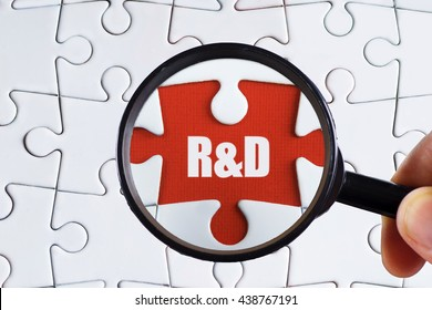 """""""R&D"""" text on red missing jigsaw puzzle with man right hand hold black magnifying glass searching for missing puzzle peace - business and finance concept"""