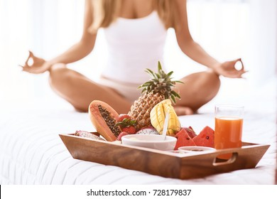Reach harmony with mind. Close up of tray with fruits in the bed while a young woman practicing yoga in the background