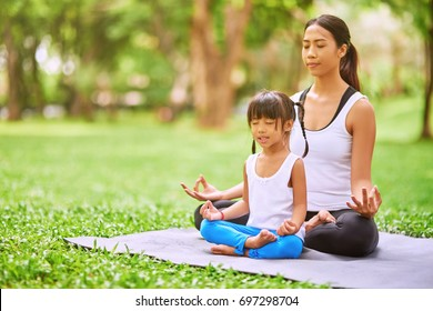 Reach harmony. Peaceful pleasant thai woman and her little daughter sitting on the roll mat and practicing yoga together in the park