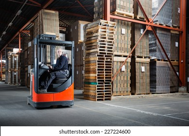 Reach truck driver in a warehouse where pallets and cardboards are stored