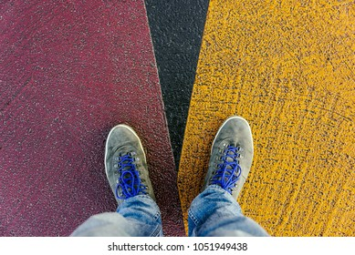 Reaching a crossroads having to decide about past, now and future symbolized by two feet and shoes standing on two different colors on pathway from above