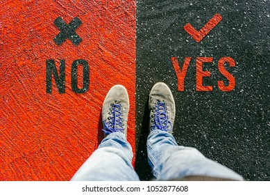 Reaching a crossroads having to decide about no and yes about future symbolized by two feet standing on two different colors on pathway from above