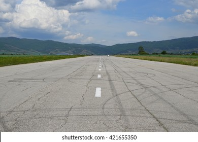 Reaching the horizon straight old tarmac runway with a car in the distance