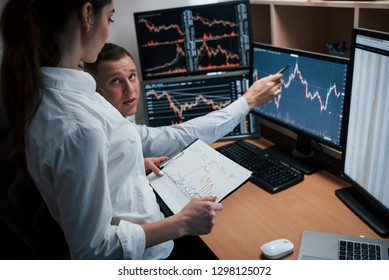 Reaching point of these two employees. Team of stockbrokers are having a conversation in a office with multiple display screens.