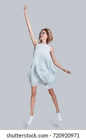 Reaching the sky. Full length of playful young woman stretching with her hand up and smiling while jumping against grey background