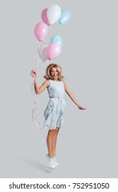 Reaching the sky. Full length studio shot of playful young woman holding balloons and smiling while jumping against grey background