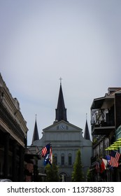 Reaching towers of Catholic cathedral arching into the sky with vintage french quarter buildings lining a street