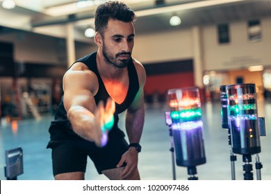 Reaction training session at gym. Athlete using a visual stimulus system to improve reaction time. Sportsman at sports science lab exercising with lights around.