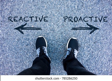 Reactive vs Proactive text on asphalt ground