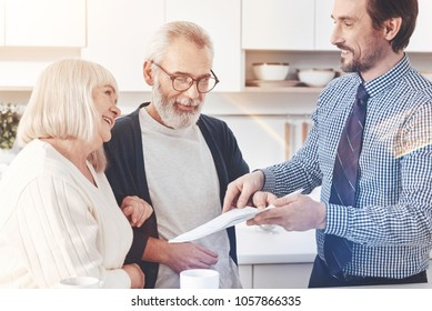 Read it attentively. Positive professional handsome real estate agent giving papers to a nice old couple while talking and meeting in the kitchen