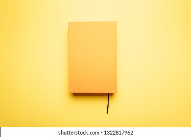 Read to the end of the literary work with a bookmark lies on a bright table. The book and the background is yellow. The concept of education.