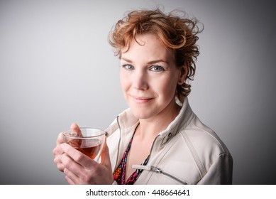 Read haired middle aged woman drinking tea. Relaxation concept. Stress free female model looking into camera.