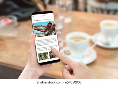 Read news article with smart phone. News portal web site with business information. Economic growth article. Coffee on table in background.