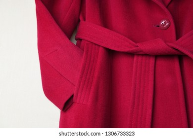 A read overcoat. Close up a fashionable women's overcoat on light background