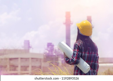 Read view of Engineering asian woman standing with yellow safety helmet and blue print in hand against oil refinery in petrochemical Aerial view oil. Industrial zone,Energy power station Background.
