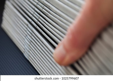 Reader thumbs through a stack on freshly printed newspapers