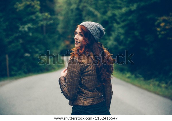 Read-Haired Woman Standing On Forest Road During Fall and Wearing a Beanie or Tuque