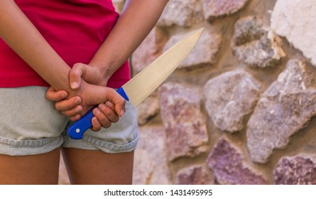 readiness for crime concept wallpaper pattern photography with empty copy space for text or inscription, young girl hold kitchen knife in behind back