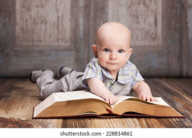 Reading.  Adorable baby boy lying on the floor reading a giant book.