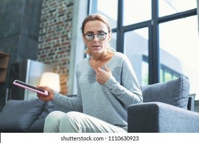 Reading away. Low angle of restless mature woman holding tablet and having hot flash