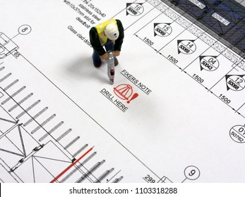 Reading, Berkshire, England - May 8, 2018, drill here fixers site note on technical drawing with construction workers drilling