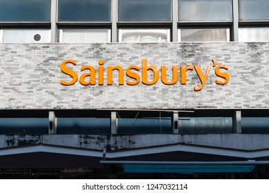 READING, BERKSHIRE, UK - NOVEMBER 30, 2018. The outside of Sainsbury's  local shop convenience store with supermarket logo in large distinctive orange lettering,