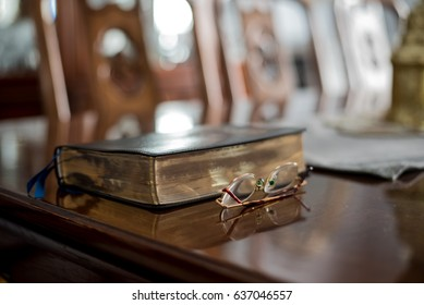 Reading the Bible with Reading Glasses on Table