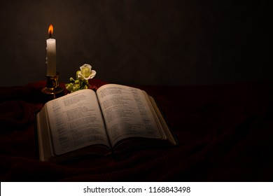 Reading the bible under the candle light on the candlestick