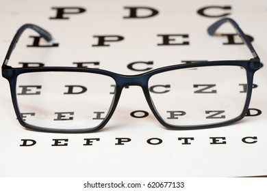 Reading black eyeglasses and eye chart close-up