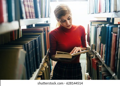 Reading a book in library. Young librarian reading a book between library bookshelves