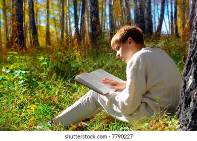 reading boy sit in autumn forest with a book