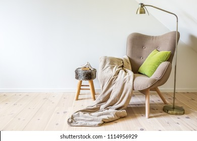 A reading chair / armchair with a lamp, blanket and a open book. Empty white wall in simple living room interior. Copy space