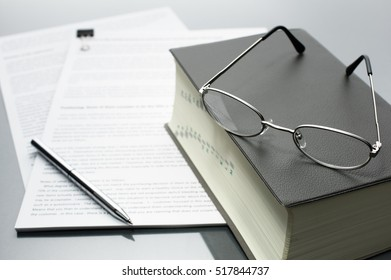 Reading and checking documents with a dictionary. Documents, dictionary, glasses and pen on gray reflection background.