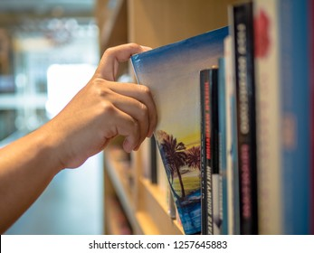 Reading concept. male hand choosing and picking book in a bookshelf. Book Travelogue, education research and self learning