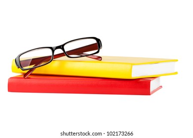 Reading concept. Red and yellow books and glasses on a white background