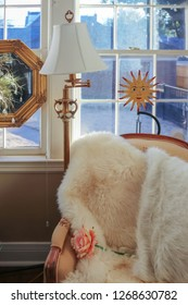 Reading corner - comfortable chair with fur throw and a rose by windows and lamp with happy sun and mirrow decor behind and outdoors seen through windows