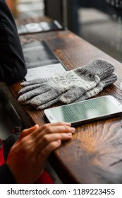 reading a digital book on a cellphone with a pair of gloves on the table in a coffee shop during winter