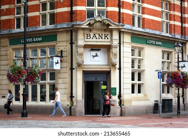 Reading, England - August 28th, 2014: A woman exits the Reading branch of Lloyds Bank as other people pass by. The UK Treasury owns 25% of Lloyds after a 20bn bailout during the 2008 financial crisis
