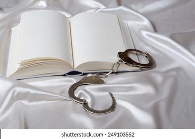 Reading erotic novel. Erotic bdsm novel concept in shades of white color.