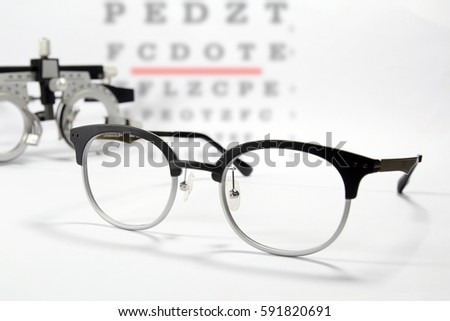 d2835a77ff Reading eyeglasses and optometrist trial frame for eye test with eye chart  background