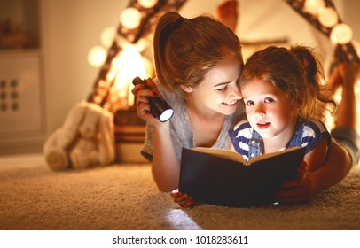 reading and family games in   tent. mother and child daughter with  book and flashlight before going to bed