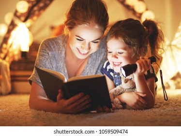 reading and family games in   tent. mother and child daughter reading book and flashlight before going to bed
