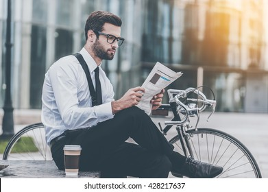 Reading fresh news. Side view of young businessman reading newspaper while sitting near his bicycle with office building in the background