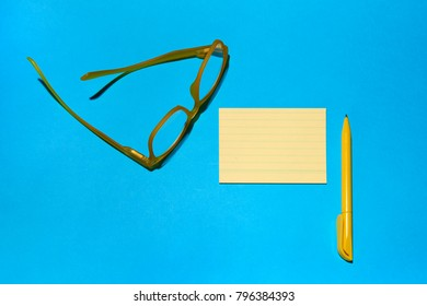 reading glasses ballpoint pen and notes all objects of yellow color on a blue background