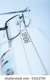 reading glasses on a folded newspaper in blue