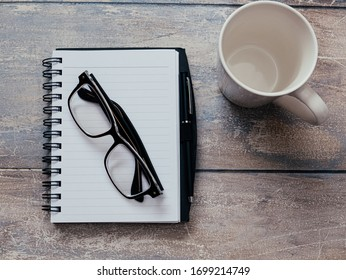 Reading glasses on top of notepad on a wooden table desk monochromatic monochrome gray