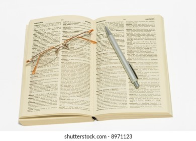 Reading glasses and pen on dictionary, pen pointing at management