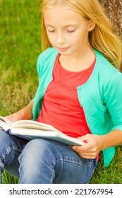 Reading her favorite book. Top view of cute little blond hair girl reading book while sitting on green grass and leaning at the tree